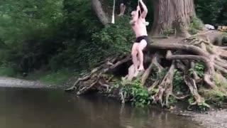 Shirtless man rope swing lands in shallow water