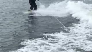 Guy water skiing in suit 2