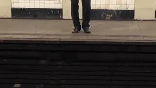 Man in grey shirt and tie singing in subway station