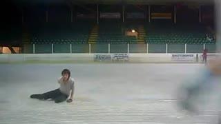 Figure skater slips and falls preparing for jump