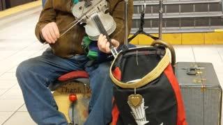Old man plays violin and cajon box in front of subway escalators