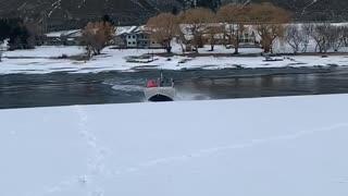 Boat Slides Through Snow Between Lakes