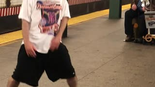 Man in white shirt dances to music from violin in subway station