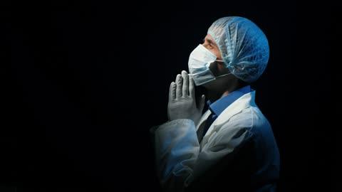 Doctor praying in a dark room looking at sky