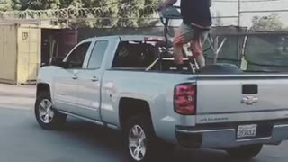 A man on a treadmill on the back of a silver truck