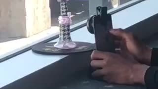 Guy trying to take picture of purple dotted bong airport airplane