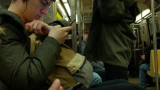 Guy quietly vogues and dances by himself on subway train