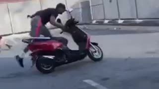 Guy does wheelie on moped bike in parking lot, scrapes floor and falls off