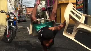 Check out this dude dancing on his hands with plastic chairs
