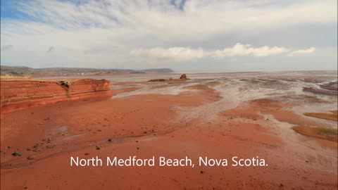 Red sand, blue skies, and white clouds