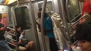 Guy blue shirt foil wings playing saxophone subway train man