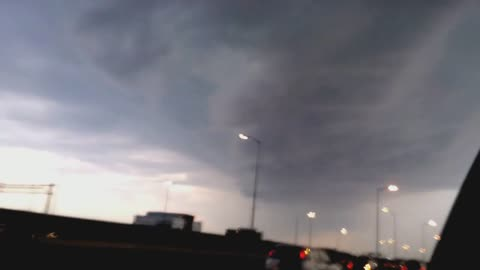 Driving in a big city and seeing a large tornado in the sky