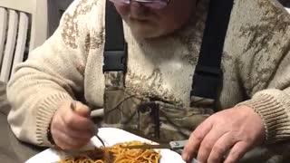 Man uses scissors to make eating spaghetti easier