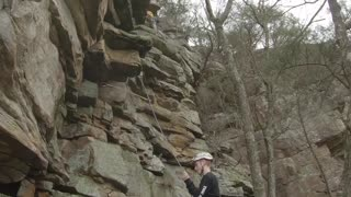 Climber, wearing a helmet, gets hit on the head with a rock.