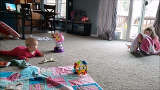 Happy baby laughs at silly big sister