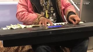 Performer on subway train plays the piano