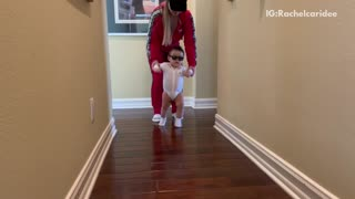 Mom helps baby dance to rock n roll song down the hall