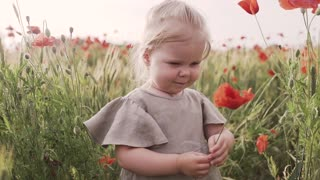 A beautiful girl is smelling a flower .