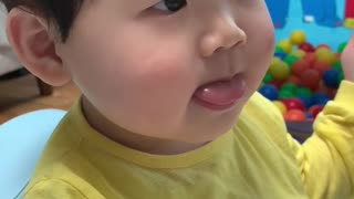 Cute baby watching TV while eating bread