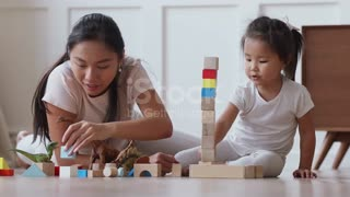 Asian mum playing with daughter building
