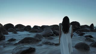 Woman walking on beach towards boulders