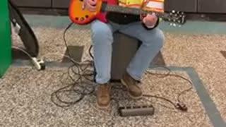 Man plays guitar station dog jumping police