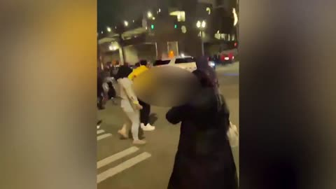rioters attack the bottom of police car