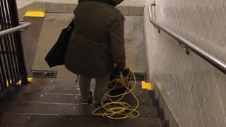 Woman pushes vacuum down public stairs
