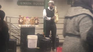 Musician in subway station playing saxophone, dancing puppets behind