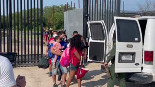 Migrants being walked through the border gate