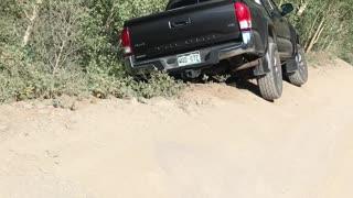 Car Hangs Precariously off Mountain Trail