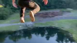 Brave guy jumps off a cliff into water