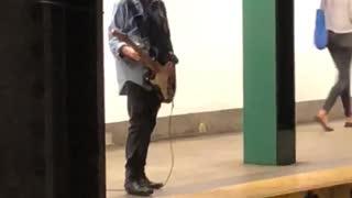 Guy denim jacket playing electric guitar subway