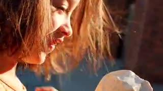 Girl Wearing an Orange Dress While Eating Ice Cream