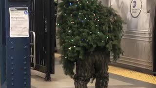 Man dressed as christmas tree walking subway station