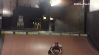 Guy does back flip on scooter at a skatepark and falls