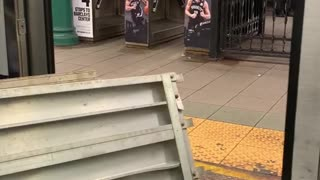 Guy carries big metal pieces into subway train