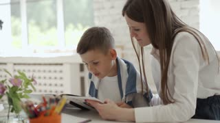 A Female Teacher Reading a Book with a Male Student
