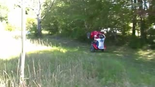 Helmet guy wheelies red four wheeler in grass and falls off