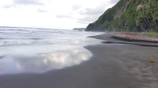 waves breaking on black sand beach