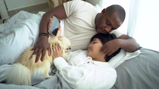 A Couple Talking while in Bed With Their Pet Dog