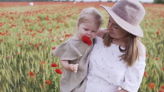 Woman Carrying Her Child While Standing on Red Poppy Flower Field