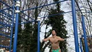 Guy does gymnastics flip on park jungle gym and falls off