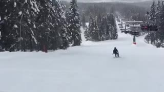 Snowboarder purple jacket falls backwards on hill