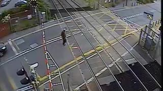Shocking moment man nearly gets hit by speeding train after lifting barrier