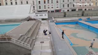Three friends do parkour in empty pool deck, guy back flips and fails