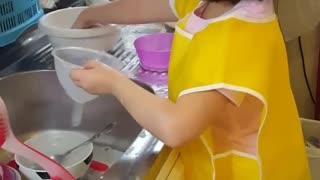 Helpful little girl loves to assist with the dishes