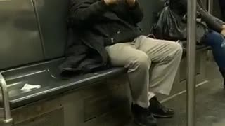 Man wearing beret plays his flute alone in a subway train