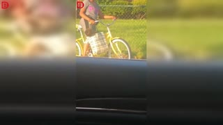 Woman rides bike with baby in bag