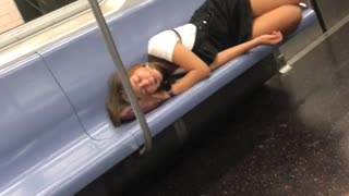 Girl with glasses asleep on her pink purse